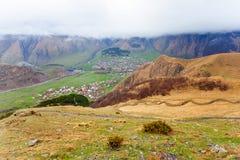 Paesaggio della montagna vicino al villaggio Stepantsminda Georgia nel primo mattino con nebbia Immagini Stock