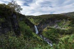 Paesaggio della penisola di Kamchatka: cascata della cascata della montagna, della vegetazione dell'alta montagna - cespugli verd Immagine Stock