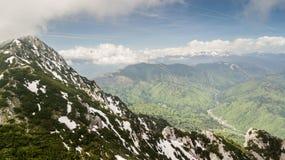 Paesaggio della primavera con i picchi di montagna coperti di neve e di nuvole Fotografia Stock