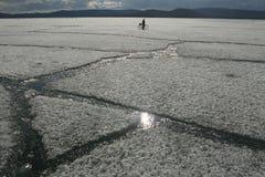 Paesaggio della primavera con la deriva del ghiaccio sul lago e un ciclista che guida su  fotografia stock libera da diritti