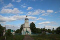 Paesaggio della primavera con una chiesa rurale sotto un cielo blu con le nuvole bianche nel villaggio di Ukhmany, Ciuvascia immagini stock libere da diritti