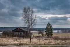 Paesaggio della primavera nel villaggio della Russia, con le case e gli alberi di legno Fotografie Stock Libere da Diritti