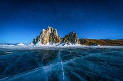 Paesaggio della roccia di Shamanka e stella sul cielo con ghiaccio tagliato naturale in acqua congelata sul lago Baikal, Siberia, fotografia stock