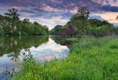 Paesaggio della sorgente al tramonto con watermill Immagini Stock Libere da Diritti