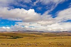 Paesaggio della terra dell'azienda agricola, delle pecore, delle montagne e delle nuvole Fotografia Stock
