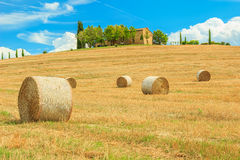 Paesaggio della Toscana, casa di pietra tipica e balla di fieno sulle colline, vicino al d'Orcia di Val, l'Italia Fotografia Stock