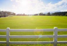Paesaggio della vista dell'azienda agricola dietro il recinto bianco e la luce giusti Fotografie Stock