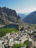 Paesaggio delle alte montagne con il lago blu, i cespugli verdi ed il bianco Fotografia Stock