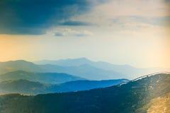 Paesaggio delle colline della montagna nebbiosa alla distanza Immagine Stock