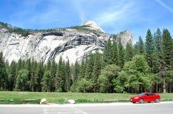 Paesaggio delle montagne con l'automobile sportiva rossa Immagini Stock