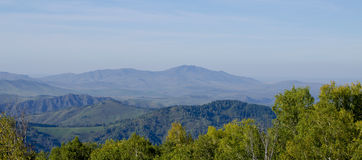 paesaggio delle montagne nella caduta fra gli alberi Fotografia Stock