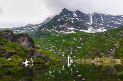 Paesaggio delle montagne riflesse nell'acqua Fotografia Stock