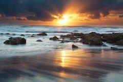 Paesaggio di alba dell'oceano con le nuvole e le rocce di onde Immagine Stock