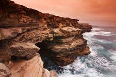 Paesaggio di alba dell'oceano con le nuvole e le rocce di onde Fotografie Stock Libere da Diritti