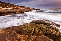 Paesaggio di alba dell'oceano con le nuvole e le rocce di onde Fotografie Stock