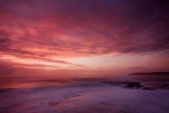 Paesaggio di alba dell'oceano con le nuvole e le rocce di onde Immagini Stock Libere da Diritti