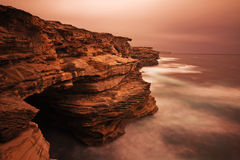 Paesaggio di alba dell'oceano con le nuvole e le rocce di onde Fotografia Stock