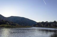 Paesaggio di autunno con il fiume e la foresta veloci lungo le banche nella sera fotografia stock libera da diritti