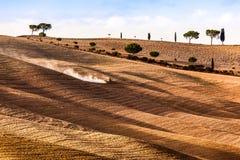 Paesaggio di autunno dei campi della Toscana, Italia Stagione del raccolto, funzionamento del trattore Fotografie Stock Libere da Diritti