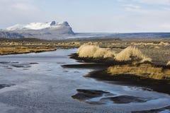 Paesaggio di autunno in Islanda con un fiume, sabbia nera Immagine Stock