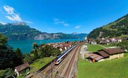 Paesaggio di estate di bello lago Lucerna un giorno soleggiato, con un treno che attraversa sulla ferrovia through il villaggio d Immagine Stock Libera da Diritti