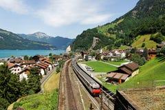 Paesaggio di estate di bello lago Lucerna un giorno soleggiato, con un treno che attraversa sulla ferrovia through il villaggio d Fotografia Stock Libera da Diritti