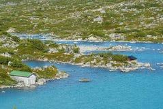 Paesaggio di estate con i cottage tradizionali ad una riva del lago in Norvegia rurale immagini stock
