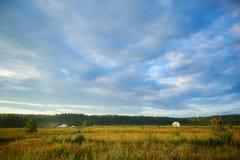 Paesaggio di estate con il campo, il cielo nuvoloso blu e un campeggio, grandangolare immagini stock
