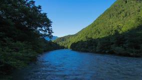 Paesaggio di estate con un fiume e le colline verdi fotografia stock