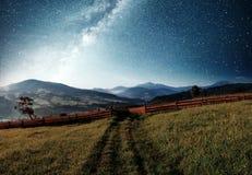 Paesaggio di estate della montagna Alta erba e cielo notturno vibrante con le stelle e nebulosa e galassia Astrophoto profondo de immagini stock