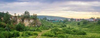 Paesaggio di estate di sera con un villaggio e la montagna, Russia, Ural Immagini Stock