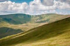 Paesaggio di estate in montagne e nel cielo blu scuro con le nuvole Fotografia Stock