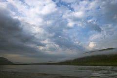 Paesaggio di giorno di estate con il fiume, la foresta, le nuvole sul cielo blu ed il sole Fotografie Stock Libere da Diritti