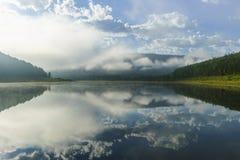 Paesaggio di giorno di estate con il fiume, la foresta, le nuvole sul cielo blu ed il sole Immagine Stock