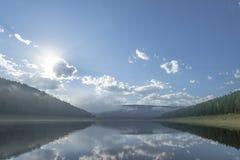 Paesaggio di giorno di estate con il fiume, la foresta, le nuvole sul cielo blu ed il sole Fotografie Stock