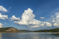 Paesaggio di giorno di estate con il fiume, la foresta, le nuvole sul cielo blu ed il sole Fotografia Stock Libera da Diritti