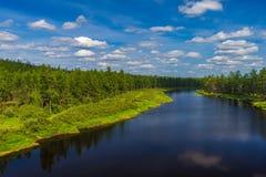 Paesaggio di giorno di estate con il fiume, la foresta, le nuvole sul cielo blu ed il sole Immagini Stock