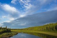 Paesaggio di giorno di estate con il fiume, la foresta, le nuvole sul cielo blu ed il sole Immagine Stock Libera da Diritti