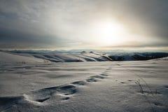 Paesaggio di inverno alto nelle tracce innevate delle montagne di viandanti che lasciano nella distanza in neve grassottella prof fotografia stock libera da diritti