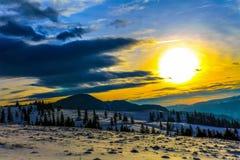 Paesaggio di inverno con la regolazione e le montagne del sole Fotografie Stock