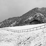 Paesaggio di inverno con le capanne di legno e montagna nella piccola v alpina Fotografie Stock Libere da Diritti