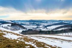 Paesaggio di inverno con neve e cielo drammatico in montagne basse immagini stock