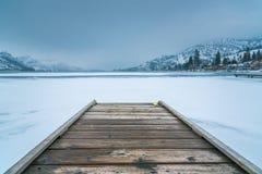 Paesaggio di inverno del bacino di legno in priorità alta sul lago congelato con le montagne e la nebbia innevate nel fondo fotografia stock