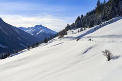 Paesaggio di inverno delle alpi del Tirolo: il pendio innevato della collina, la strada della campagna e due genti stanno cammina Fotografie Stock