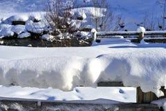 Paesaggio di inverno delle alpi del Tirolo: inferriata di legno innevata, piccolo fiume della montagna su fondo Fotografia Stock