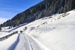 Paesaggio di inverno delle alpi del Tirolo: la strada innevata sul pendio della collina, due genti sta camminando Fotografie Stock Libere da Diritti