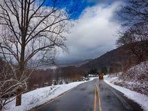 Paesaggio di inverno e strade innevate nelle montagne Immagini Stock