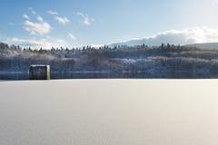 Paesaggio di inverno, lago con una diga nella priorità alta, contro la foresta ed il cielo nuvoloso blu, bella natura, Ucraina oc Fotografie Stock