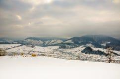 Paesaggio di inverno, montagne della neve, alberi su un fondo del blu Fotografie Stock