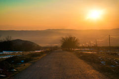 Paesaggio di inverno o di autunno con la strada e gli alberi Il tramonto dei raggi luminosi dell'oro Su un fondo delle montagne e Immagini Stock